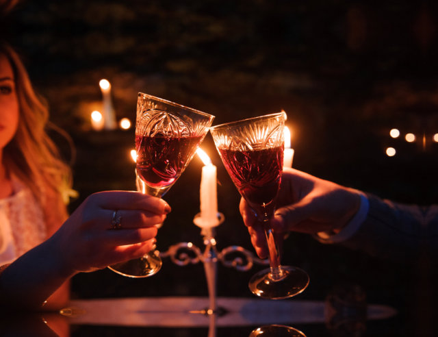 couple cheers their glasses of wine